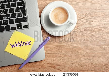 Webinar written on sticky note, laptop and cup of coffee on table, top view