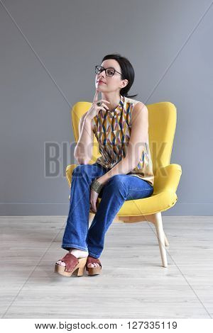 Woman in armchair with serious look; isolated