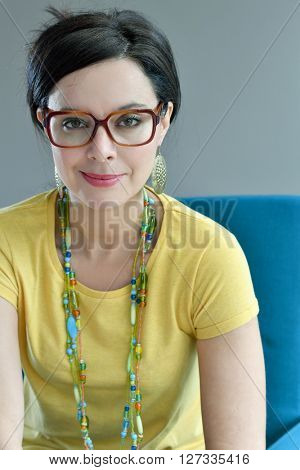 Smiling trendy girl sitting in blue armchair, isolated