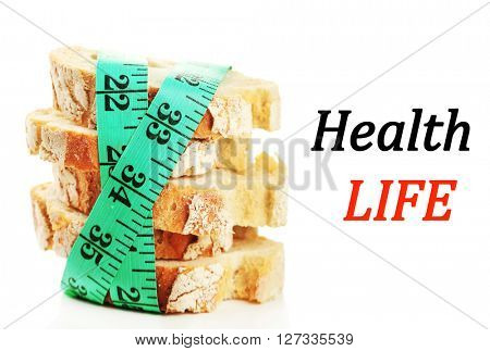 Fresh bread with measuring tape isolated on white. Health and diet concept