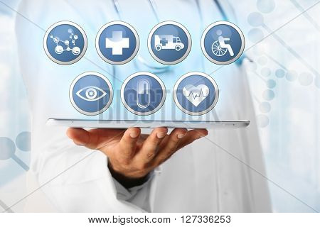 Doctor hand and tablet with medicine icons. Medical technology concept