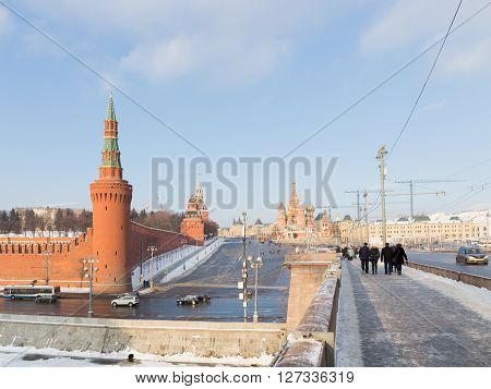 Moscow - January 7 2016: People walk by and large Moscow River bridge and see the Kremlin Vasilevsky descent and St. Basil's Cathedral in winter January 7 2016 Moscow Russia