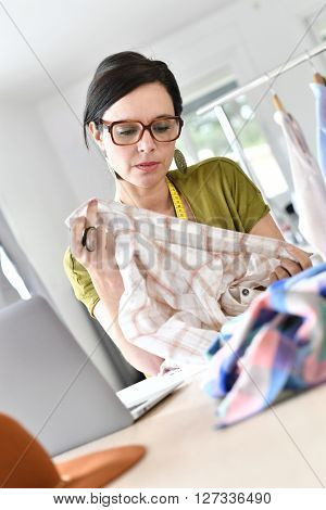 Fashion designer in office working on cloth