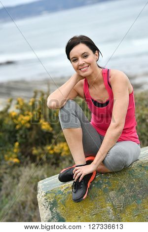 Woman in fitness outfit relaxing after exercising