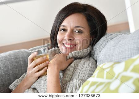 40-year-old woman relaxing in sofa with cup of tea
