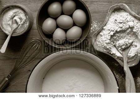 flour eggs whisk in a cup of kefir and for the preparation of dough. view from above close-up. black and white photo