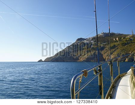 Handrail of boat against a rock and sky