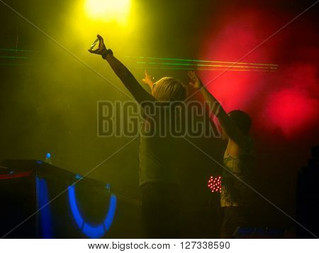 Two deejays upraising his arms against many-coloured lights