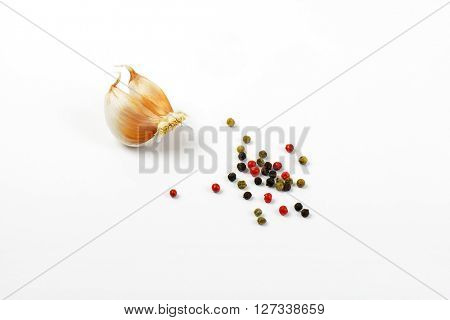 cloves of fresh garlic and peppercorns on white background