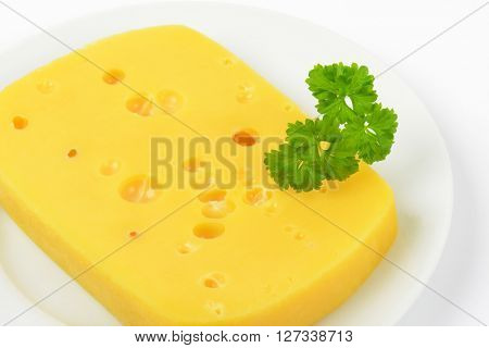 close up of emmental cheese with holes on white plate