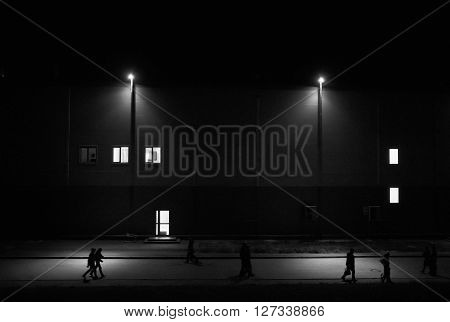 People walking on the night street with streetlights against the building with luminous windows