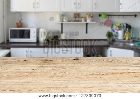Old wooden oak table in the foreground and white modern kitchen is blurred in the background