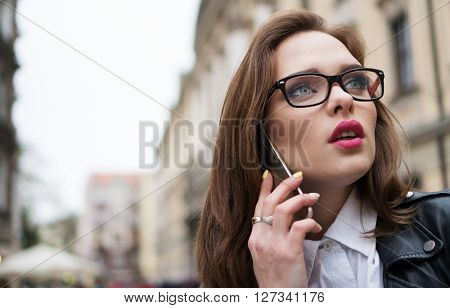 pretty woman in the city speaking using smartphone in  the town