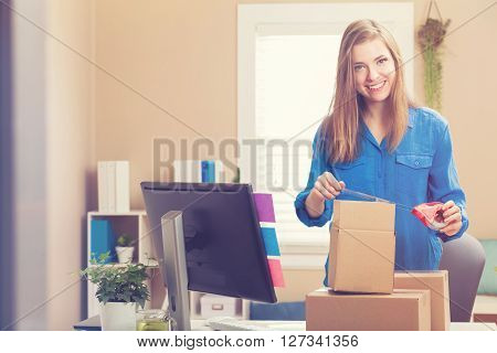 Woman Taping Boxes To Be Shipped In Her Home Office