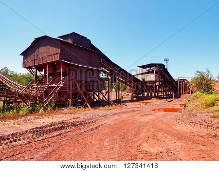Small crushing metal ore plant under blue sky