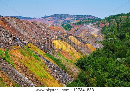 Outside the open cast mine with trees beside colorful depleted iron ore dumps and road on the background