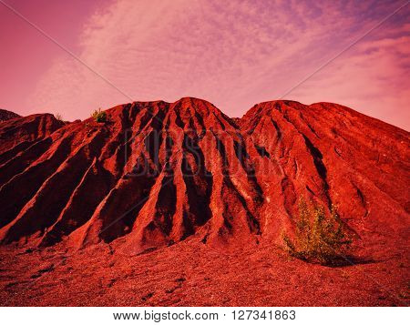 Red toned landscape with heap of depleted iron ore and the tree under the cloudy sky