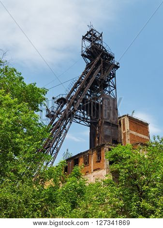 Abandoned iron ore mine headhear behind of green trees