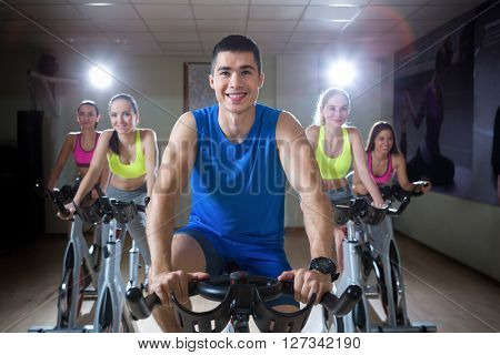 Smiling people on cycle indoors
