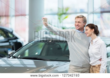 Young couple making selfie at cars