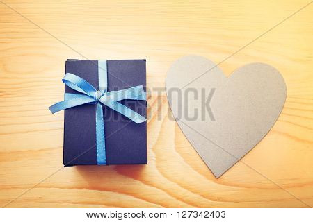 Giftbox And Hand Cut Heart On Wooden Table