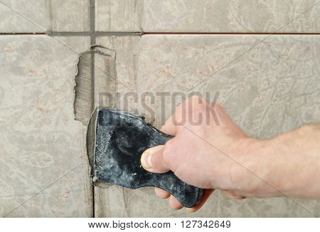 The hand of man holding a rubber float and filling joints with grout.