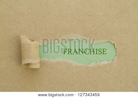 FRANCHISE word written under brown torn paper.