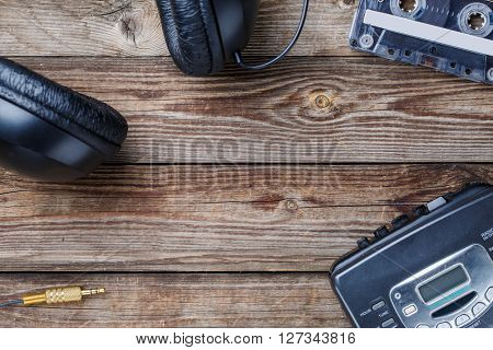 Cassette tapes, cassette player and headphones over wooden table. top view.