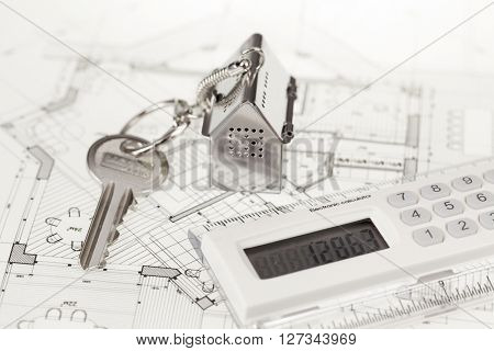 key with keychain in the form of a silver-colored house on a background of architectural drawing & electronic calculator
