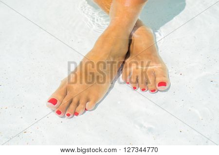 Female legs in the pool water selective focus and motion blur