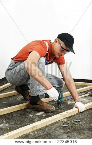 Worker twists the screw fixing wooden beams.
