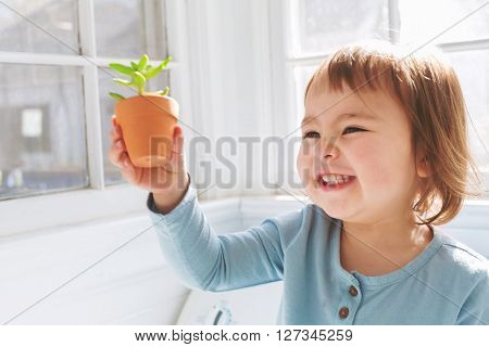 Happy Toddler Girl Playing With Potted Plants