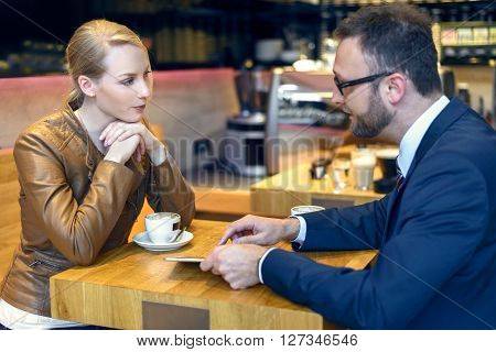 Businessman And Woman Sitting Down To Coffee