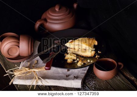 Piece of pie and pottery for tea on an old wooden table. Style