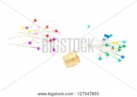 Colored Pins And Thimble On White
