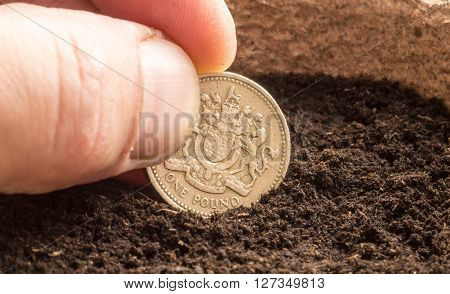 Human Hand Sowing A Pound Coin In Compost