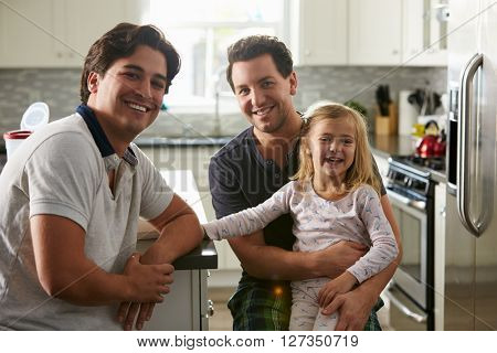 Male gay couple sitting with their daughter in the kitchen
