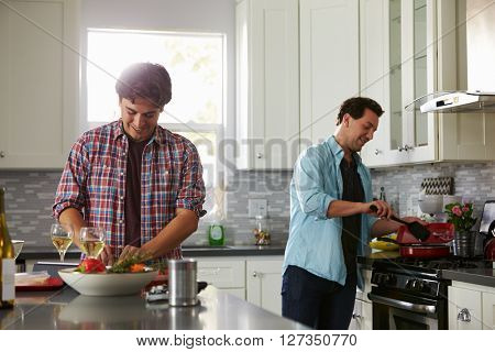 Man chopping while his boyfriend cooks ingredients in a pan
