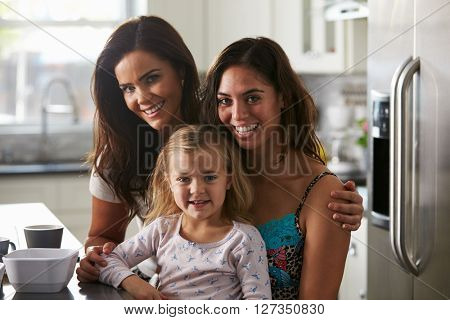 Portrait of female couple in the kitchen with their daughter