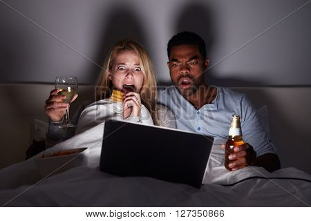 Mixed race couple watching scary film in bed on laptop