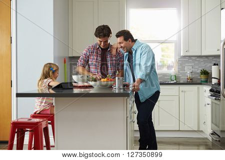 Daughter sits in kitchen while her male parents prepare meal