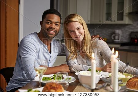 Romantic mixed race couple look to camera at meal in kitchen