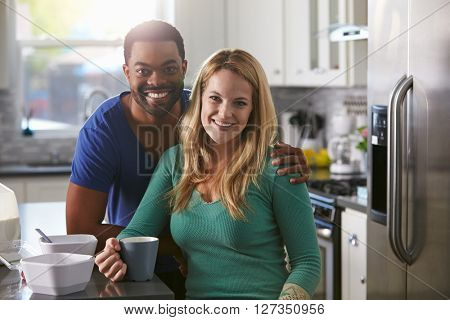 Portrait of mixed race couple in kitchen, man leaning down