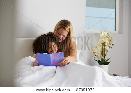 White mum and black daughter looking at card, full length