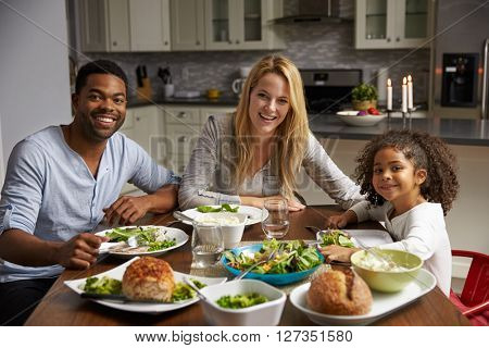 Girl and mixed race parents dine in their kitchen, to camera