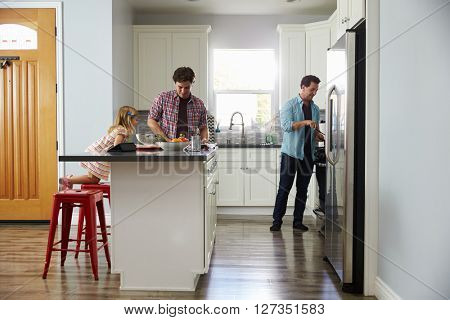 Daughter in kitchen watches her male parents prepare meal
