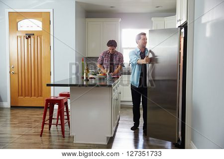 Male couple in the kitchen preparing a meal, opening fridge