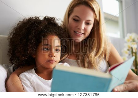 Caucasian mum and black daughter read book in bed, close-up