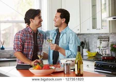 Smiling male gay couple drinking wine while preparing a meal
