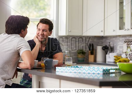 Male gay couple in their 20s talking in their kitchen